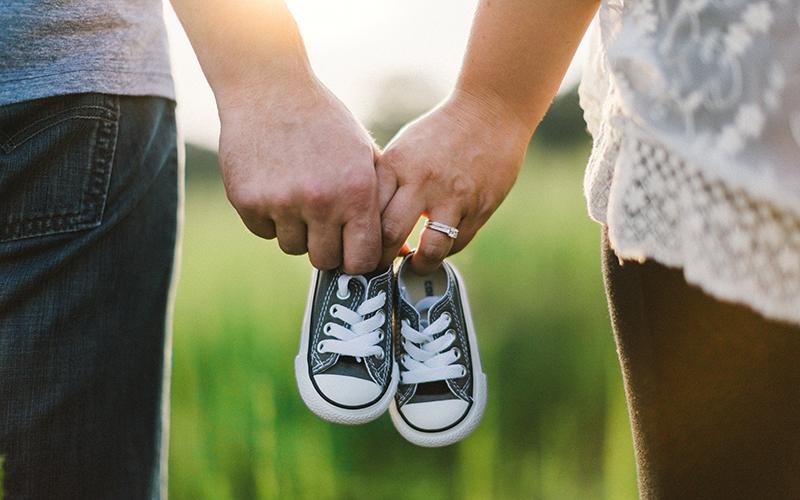 Un couple tient une paire de chaussures de bébé dans la campagne.